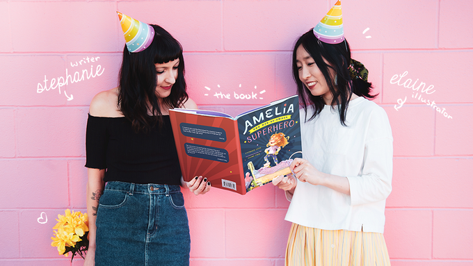 Vancouver author Stephanie Lecce and illustrator Elaine Chen standing in front of a pink wall and holding their children's book, Amelia the Not-So-Small Superhero